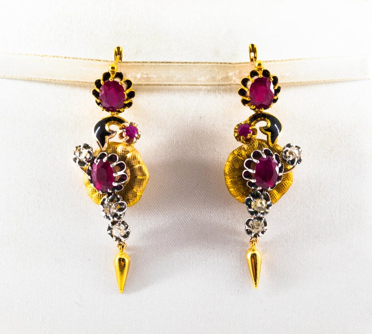 These Lever-Back Earrings are made of 9K Yellow Gold and Sterling Silver. These Earrings have 0.90 Carats of White Rose Cut Diamonds. These Earrings have 4.00 Carats of Rubies. These Earrings have also Black Enamel. All our Earrings have pins for