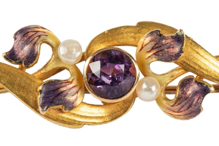 Of gold foliate design enhanced with violet enamel petals, two pearls and a central amethyst. The early 20th century American pin has added antique value and is in excellent condition.  Krementz, Newark, circa 1900.  1 1/2 in (3.8 cm) long