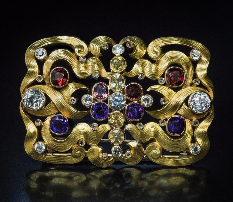 Made in Moscow between 1899 and 1908.  This unique, one of a kind, 14K gold Art Nouveau belt buckle / brooch is designed as interlacing ribbons accented by bezel-set white sapphires, Siberian amethysts, almandine and rhodolite garnets, aquamarines,
