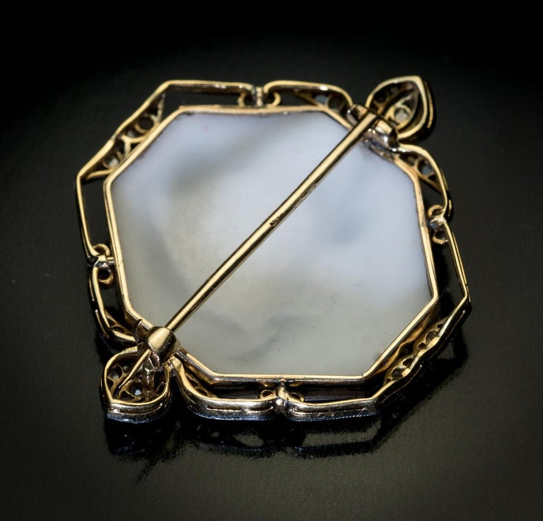 Vienna, circa 1910  This elegant Art Nouveau era brooch/pin features a multi-layer shell cameo finely carved with a profile of a female wearing a tiara. The cameo is set in an openwork platinum topped 14K gold frame embellished with old rose cut