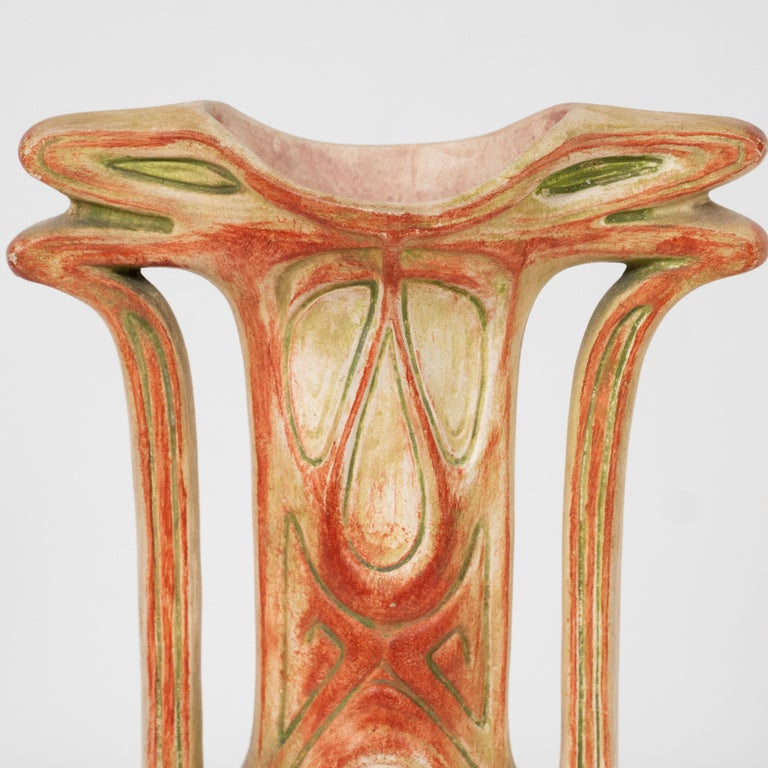 This stunning and graphic ceramic vase was realized in Austria by Julia Dressler at the beginning of the 20th century. It features a conical body that ascends into a cylindrical neck that flares out at the mouth. The piece has sinuously curved and