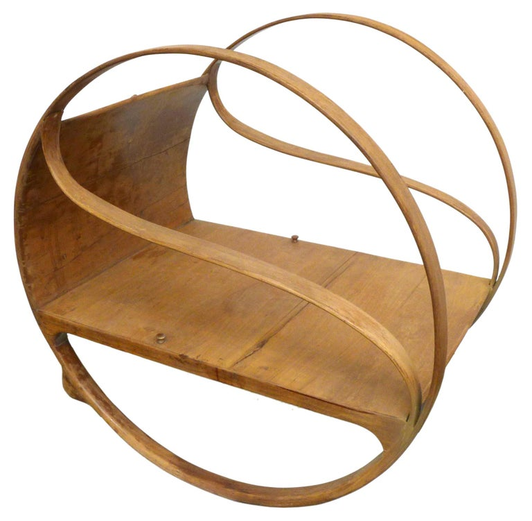 An incredible and unusual Art Nouveau bent sandalwood rocker. A beautifully-built, elegant and highly-unexpected construction, two 3' bentwood rings flank and support an unusually deep seat with concave back. Carved wood buttons at the seat and