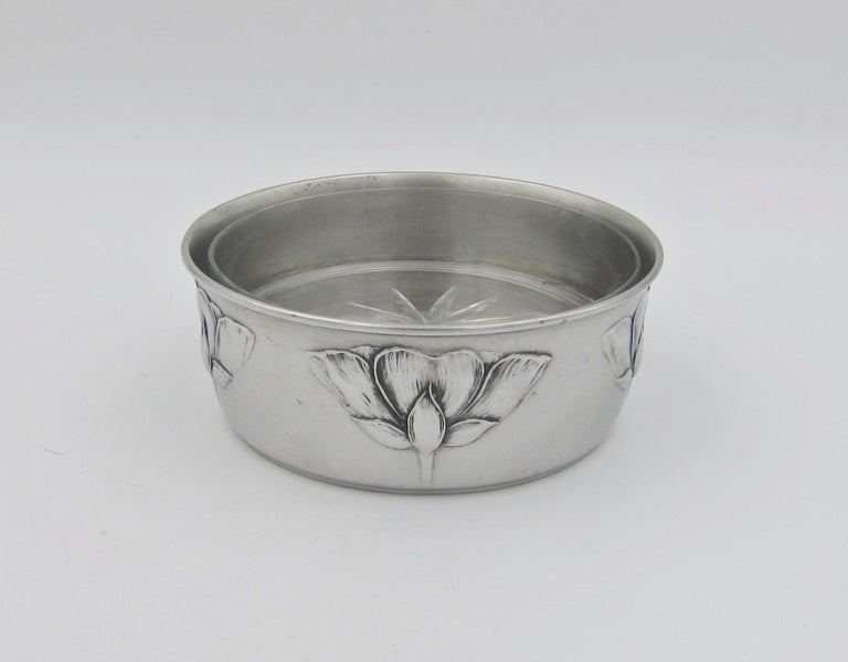 An antique Kayserzinn pewter champagne and wine bottle holder or coaster from Germany dating to the early 1900s. The gleaming, silvery-gray surface is decorated with low relief blossoms in the Art Nouveau style. The bottle holder retains its