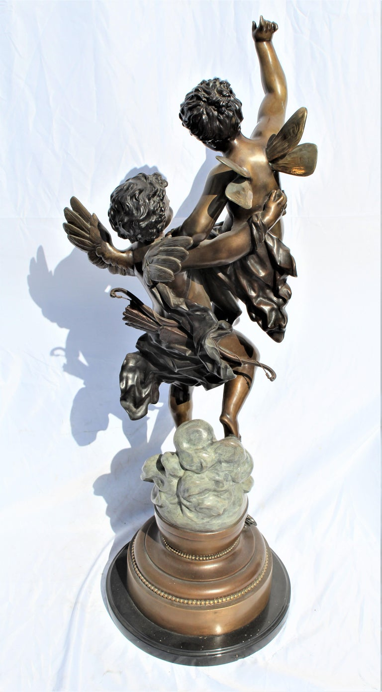 Great looking large bronze sculpture of winged pixy held by a Cherub floating on the clouds. Multi-patinas with fine details. Made from the original. Bears the signature at base. The title is the Triumphator.