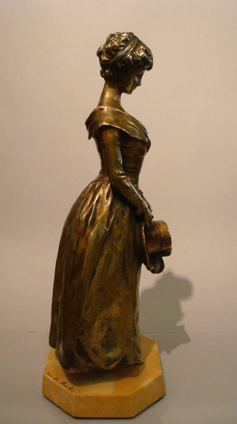 Late 19th century bronze by Belgian sculptor Georges Van der Straeten (1856-1941) depicting a stylish young maiden standing with a hat on her hands. Signed Van der Straeten on base , numbered under the figure.  Seal of the importer that sold it in