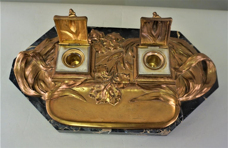 An amazing work, double inkwells in red coopery color bronze with flower and leaf accents and marble base.