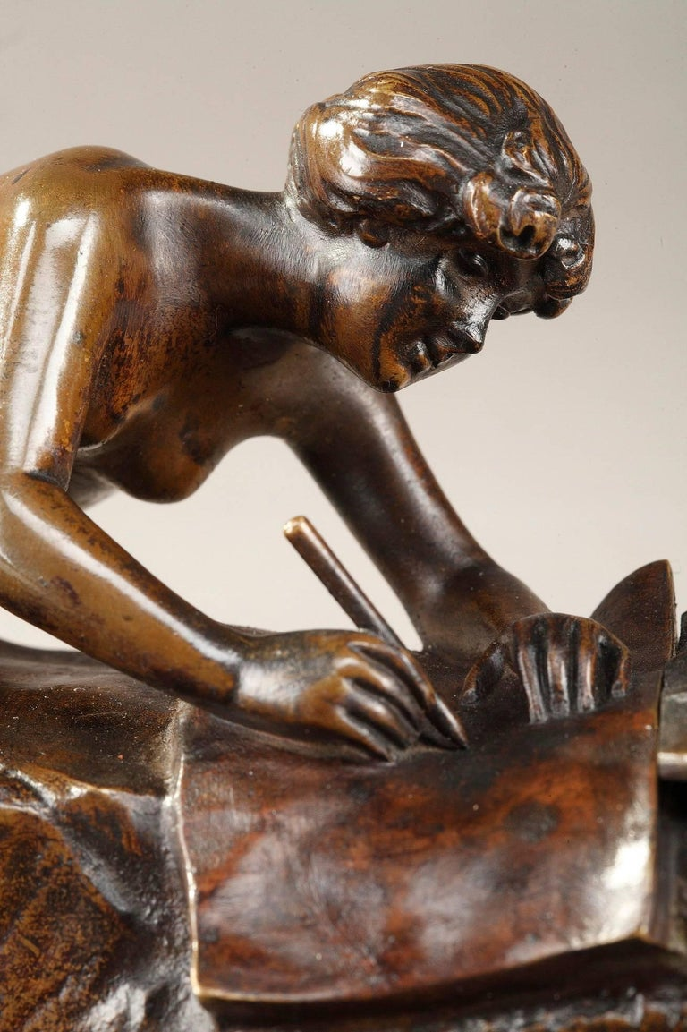 Small patinated bronze sculpture forming an inkwell and representing a young nymph writing, lengthened on a bed of reeds and plant motifs. By Karl (Charles) Korschann (Czech, 1872-1943). The buckets for ink are hidden under two large leaves. The