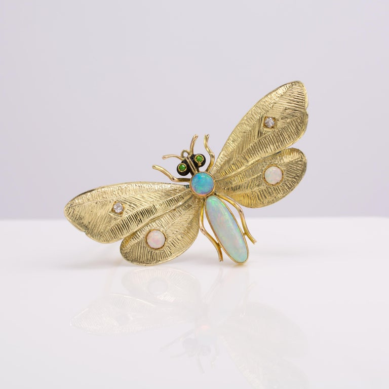This outstanding Art Nouveau butterfly brooch features natural opals diamonds and demantoid garnets. Circa 1910  Hallmarked 14 Karat gold with a patent date of nov. 30 '86(1886)  This beautiful piece is offered in very good condition. The opals are