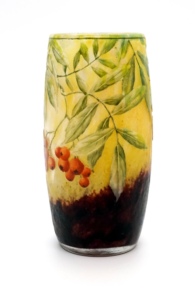 Cylindrical vase, colorless glass with flaky yellow and white, in the stand area with blackberry-colored powder melts, satined, structured surface with etched sea buckthorn decoration painted in polychrome enamel, relief signature 'Daum Nancy' with