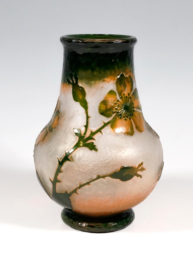 Vase in a bulbous shape with an offset round base, wide neck that tapers towards the top with a slightly flared mouth rim, colorless glass with a milky, opaque inner melting's in the lower area, dark green and orange to rose-colored melting's in the