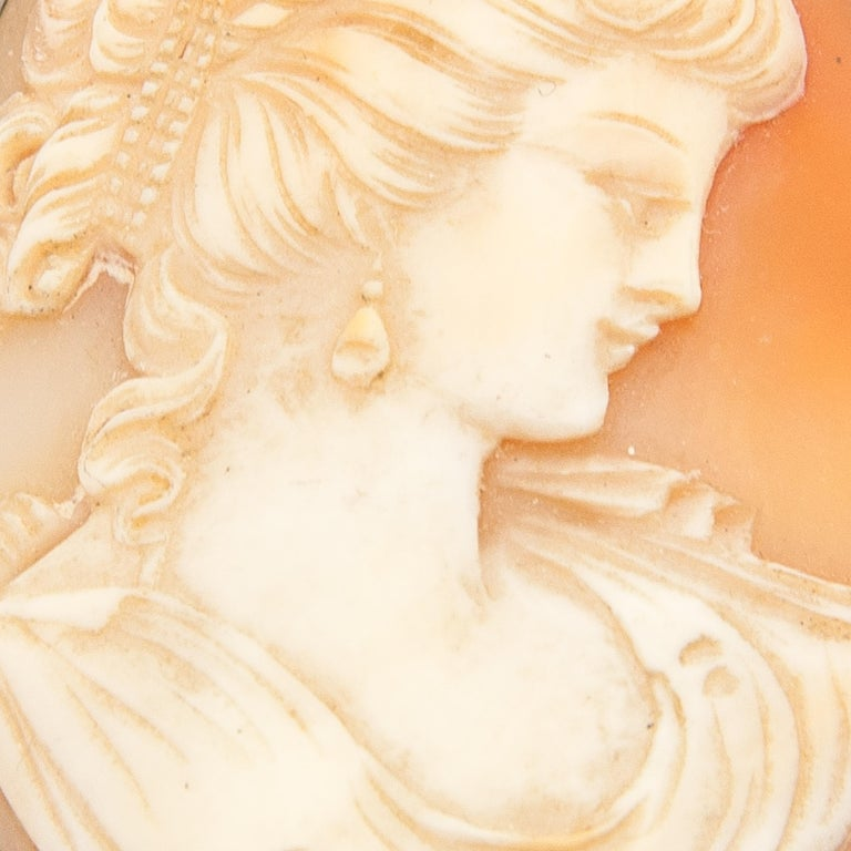 Art Nouveau-style shell cameo brooch with a fine and detailed female silhouette. This lady radiate pure beauty. Her curly hair is beautifully detailed with a ribbon in her hair and wearing drop earrings. The carved shell is set in a silver setting
