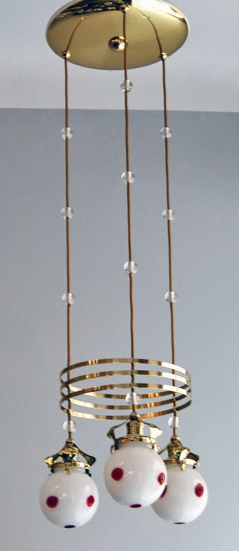 Most elegant Art Nouveau ceiling lamp or chandelier with three bulbs made by Bakalowits & Sons. Vienna (Austria), manufactured circa 1905-1910.  Specifications: Three bulbs made of glass - each of them having decorative red spots melted on white