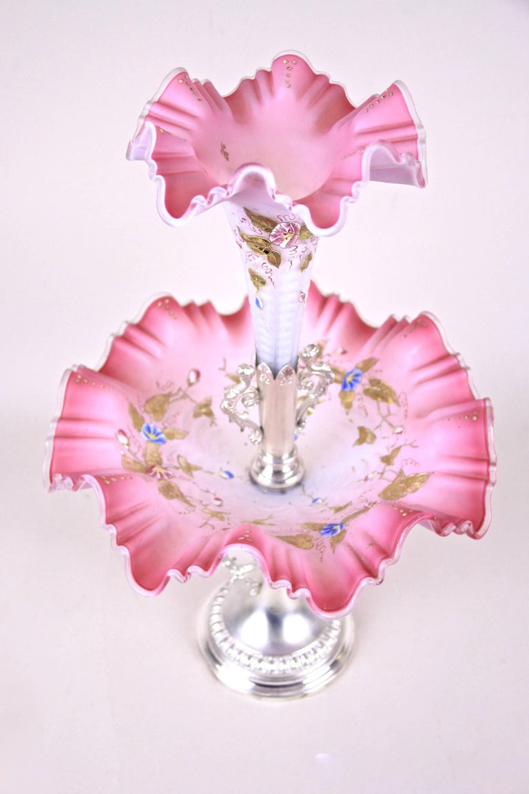 Charming Art Nouveau centrepiece made in Austria, circa 1900. A beautiful in pink tones shining mouth blown glass bowl sits on a metal - silver plated centrepiece with figural handles and shows an amazing enamel-painting that continues on the