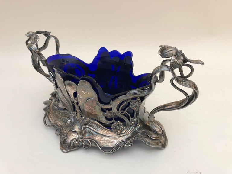 This ravishing Art Nouveau silver plated centrepiece is decorated with butterflies, flowers, and budding tendrils, and retains the original applied patina and cobalt-blue-glass liner. Designed by the German sculptor Albert Meyer, it bears the stamp