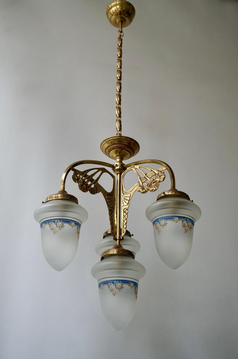 Elegant Italian brass Art Nouveau chandelier with four painted glass shades. Measures: Diameter40 cm. Height fixture 50 cm. Total height including chain 110 cm.