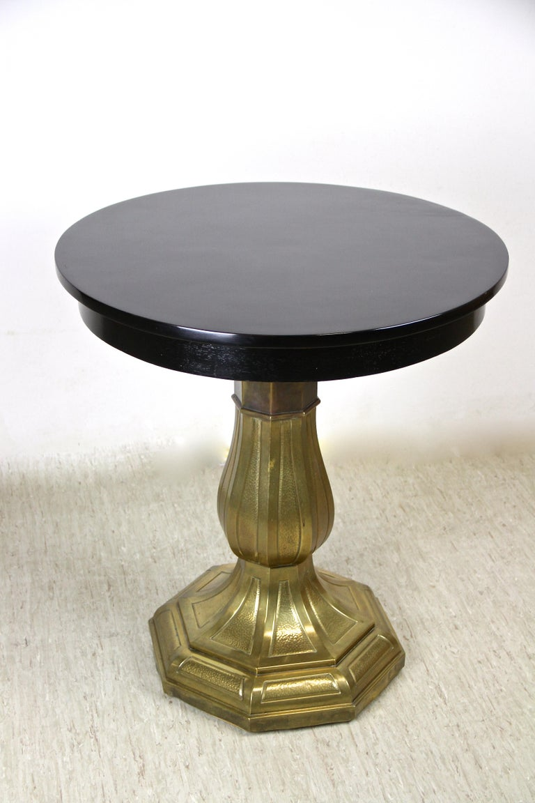 Remarkable black lacquered Art Nouveau coffee/ side table out of Vienna/ Austria from the period circa 1910. The glossy round tabletop sits on an artfully shaped column with an octagonal base. A brass/ copper coated masterpiece impresses with a