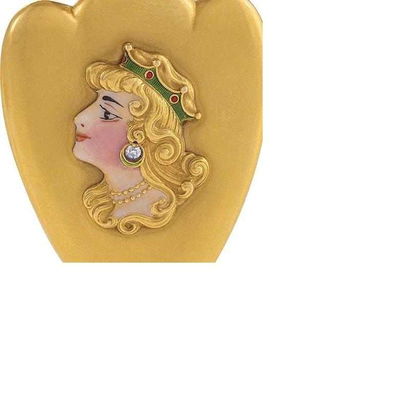 An American Art Nouveau enamel, 14 karat bloomed gold and diamond pendant locket. The figure on the heart-shaped pendant locket wears an old European-cut diamond 'earring' with an approximate weight of .04 carat.  The uniquely shaped pendant locket