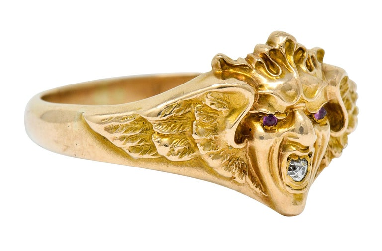 Band style ring with a highly rendered green man motif, featuring a grimacing face topped by a foliate crown  Flanked by spread wings with intricate feather detail and texture  Eyes are accented by small round cut rubies while mouth holds an old