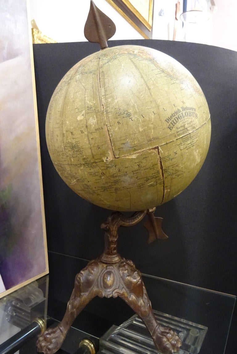 Stunning Earth globe by Dietrich Reimers, Berlin 1913, with arrow and foot with masks in wrought iron.