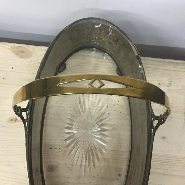 The brass body of the centerpiece is formed by a band pressed with arabesque motifs, intervalled with smooth rosettes, the feets are in the shape of an ovalizzed sphere, on the band is applied an elegant handle pivoted so as to be movable and