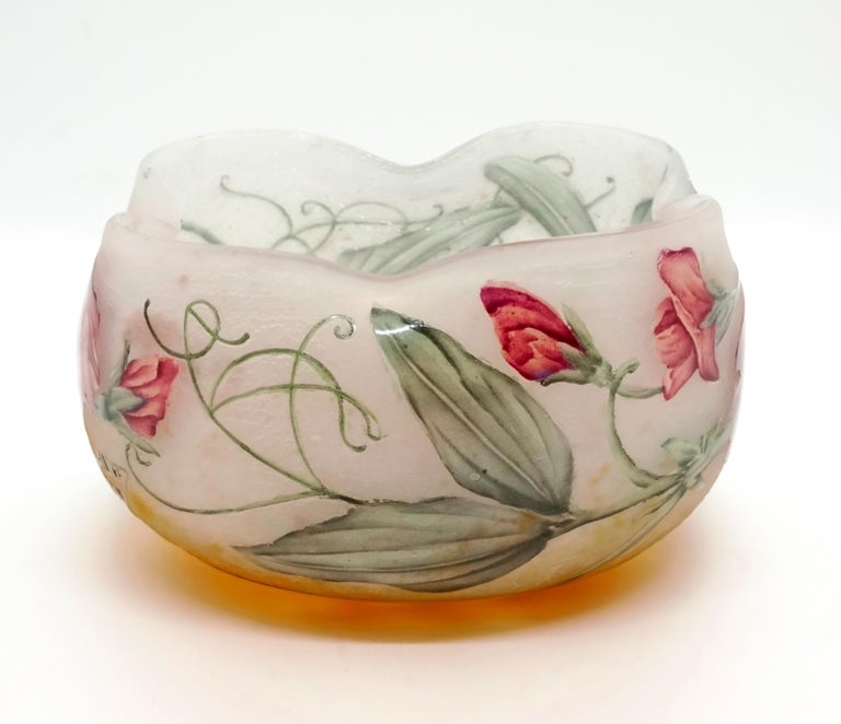 Round bowl with four-fold depressed opening, colorless glass with yellow powder fusions in the Stand area, satined, structured surface with etched and colored enameled sweet pea decoration, relief signature 'Daum Nancy' with the cross of Lorraine on