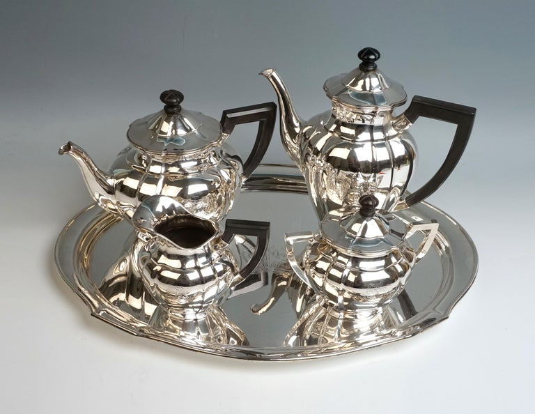 Elegant 5-piece silver centerpiece consisting of coffee and teapot, milk jug, sugar bowl and tray. Oval basic shape, bulging wall of the vessel body, vertically divided by pilaster-like folds. Coffee and teapot with swan spout and hinged covers with