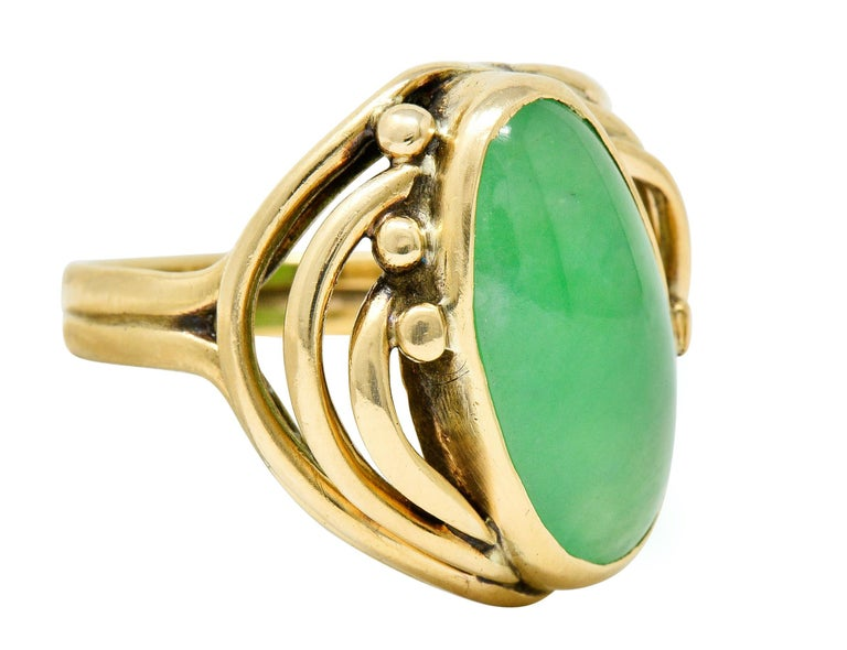 Band ring centers an elongated oval jadeite jade cabochon; measuring approximately 16.5 x 19.2 mm  Translucent with uniform green color with no indications of impregnation; type A jade  Surrounded by arched whiplash branches terminating as gold bead