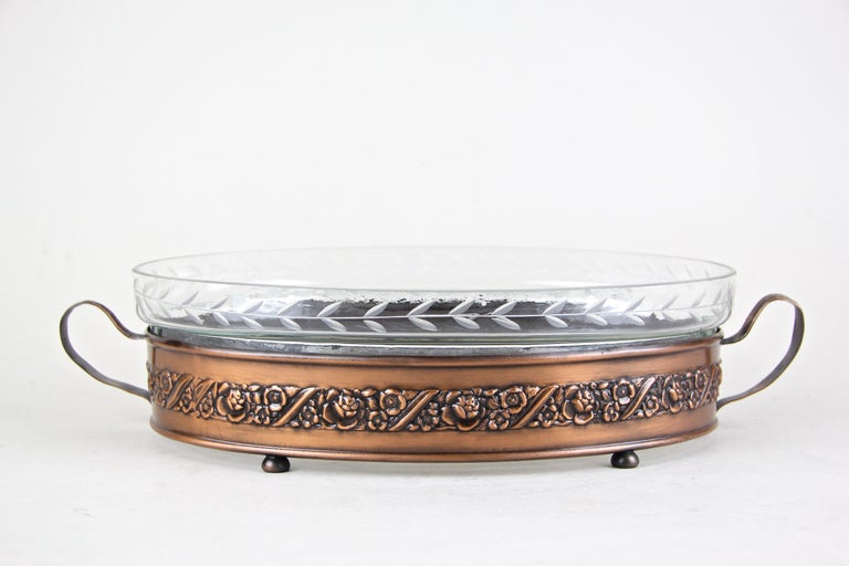 Made of fine copper, circa 1915, this beautiful Art Nouveau jardinière from Austria impresses with a great embossed design adorned by classical roses. The inserted cut glass bowl comes with overhanging ornamented edges and a small engraved star in