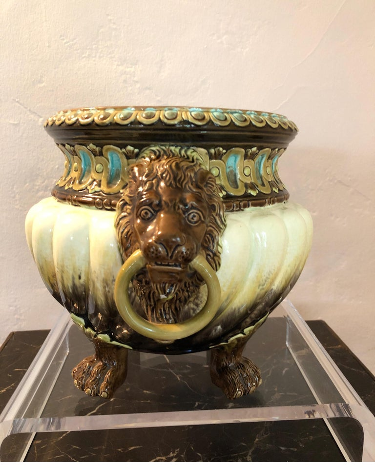 Eye-catching Art Nouveau jardinière by Julius Dressler. Stamped and numbered on bottom.   Gorgeous shades of greens, teal and brown with lion heads holding rings.   Beautiful representation of Majolica.