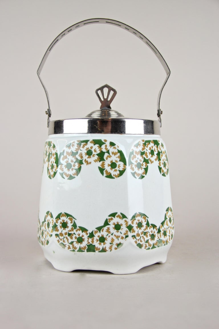 Lovely Art Nouveau lidded ceramic jar from Austria, circa 1915. This piece from the early 20th century shows a beautiful cherry blossom design in green and light brown. A nice chromed mounting with perforated handle and a great designed lid makes