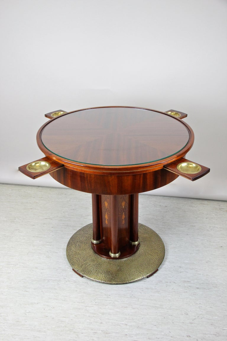 Remarkable Art Nouveau mahogany gaming table out of Vienna/ Austria from the early 20th century circa 1910. The round tabletop, covered by a protecting glass plate, sits on a quadratic column adorned by elaborately fruitwood inlay works on all four
