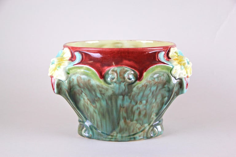 Colorful Art Nouveau Majolica cachepot from the early period in France around 1910. The lovely floral design with three big blossoms in light blue and yellow harmonizes perfectly with the unique shaped turquoise, green and red hand painted body. A