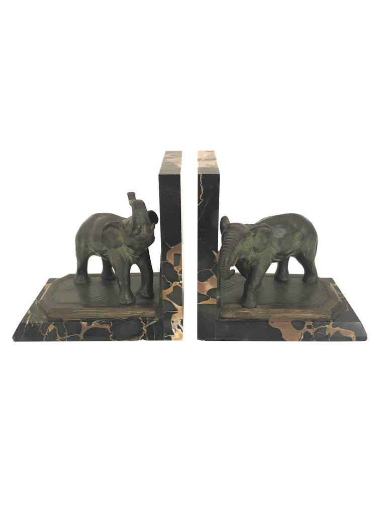 Bookends with elephants in two different poses By Albert Marionnet (1852-1910), signed France, circa 1900.  Material: – Bronze, original patina – Portor-marble socle   Dimensions:  Width 14.5 cm  Height 14.5 cm  Depth 9.5 cm.