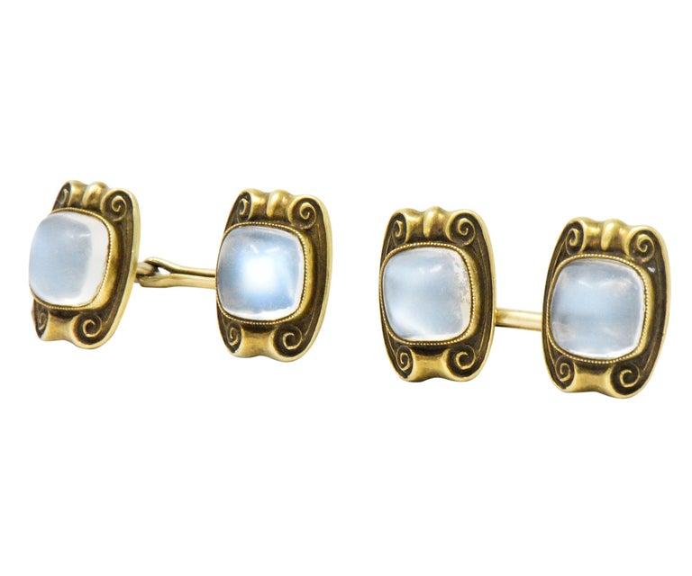 Each centering a square cabochon cut moonstone measuring approximately 8.4 x 8.5 mm  Beautiful billowy silver blue  Bezel set with millegrain and scrolling gold detail  Chain link style cufflink  Measuring: 13.9 x 10.5 mm  Total Weight: 10.8