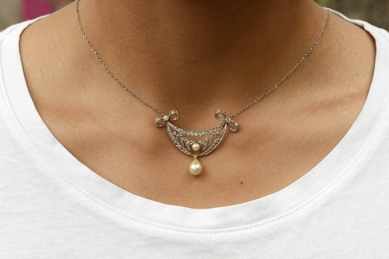 What a wonderful, wearable, Art Nouveau natural pearl and diamond necklace. The drop floral motif floral adorned with filigree garlands and bows is encrusted with sparkling old cut diamonds. Centered with a lustrous, white round pearl, the lavaliere