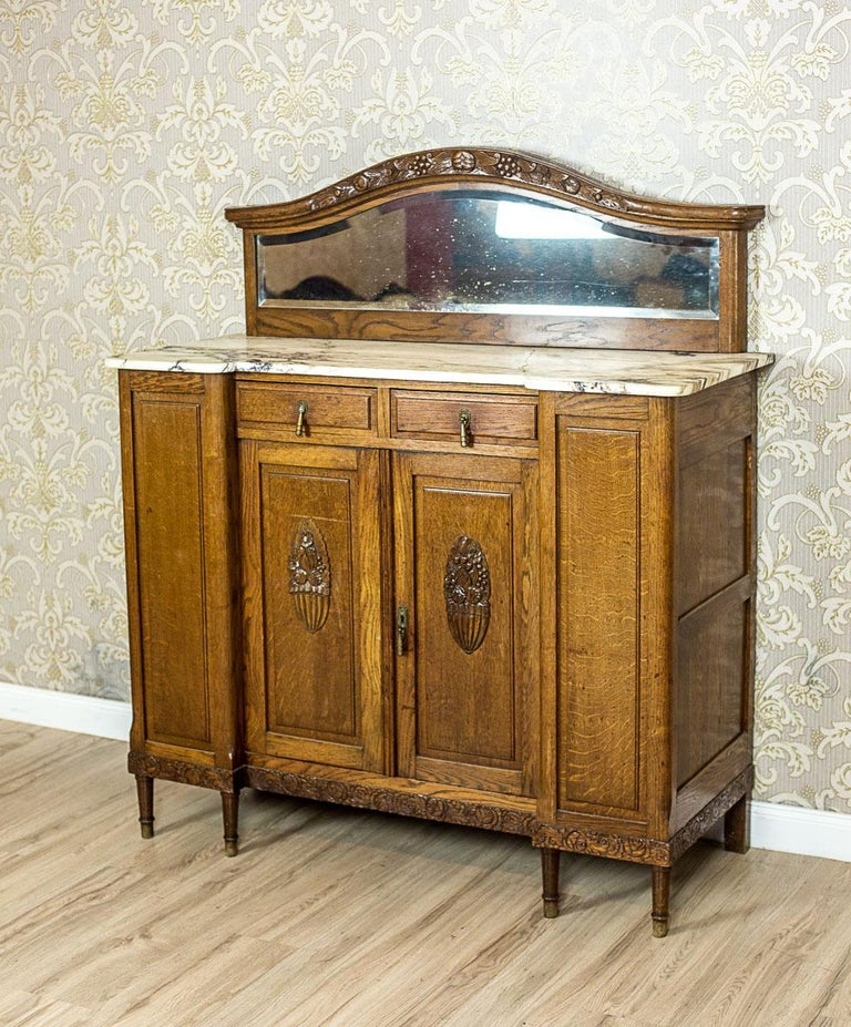 We present you this piece of furniture, circa early 20th century, made entirely of solid oak wood.