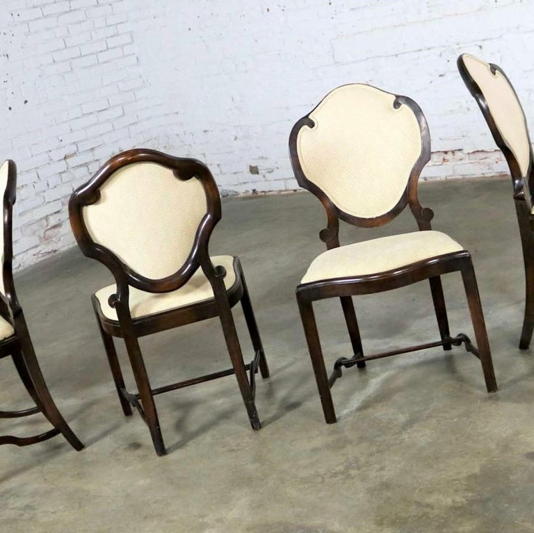 Incredible Art Nouveau or Art Deco set of four dining chairs with shield shaped backs and lots of detail. They are in wonderful original antique condition. They are very solid. The wood frames have lots of beautiful age patina including nicks and