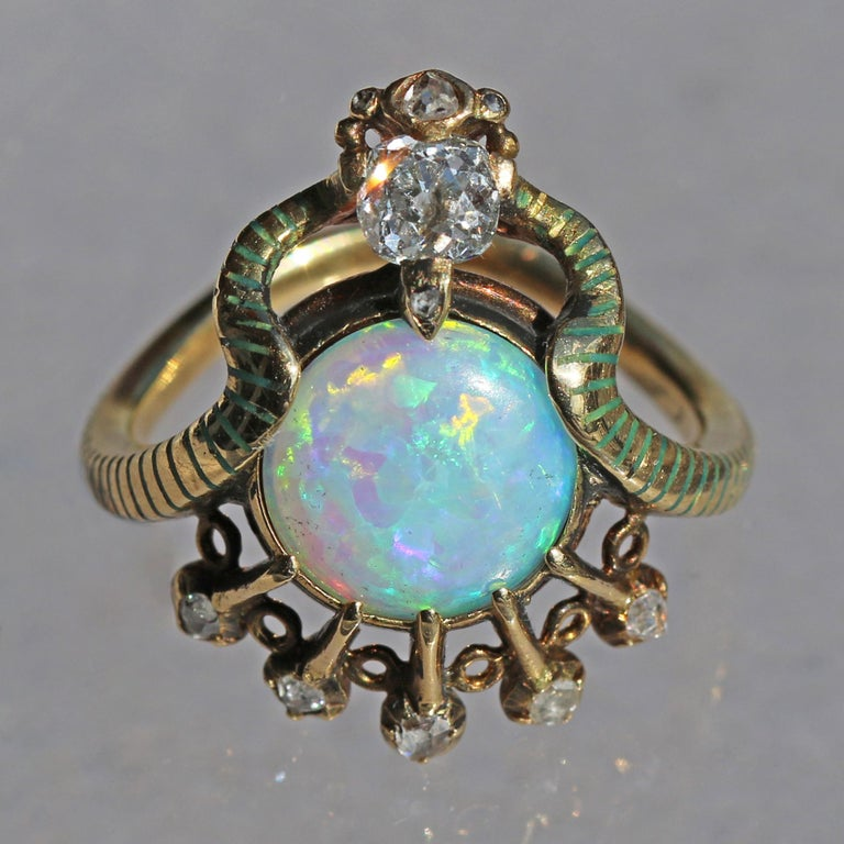 This unique and exceptional ring is astonishing in its concept. The sinuously entwined snake with its green champlevé enamel stripes has an affinity with ancient Egyptian rings, as does the fine cabochon opal to the solar disc Aten. A fabulous