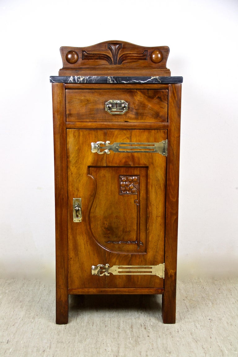 Charming Art Nouveau pillar commode from the very early 20th century in Austria. Made around 1905, this eye-catching compact pillar commode shows a lovely nut wood veneered surface adorned by beautiful brass applications. The door, adorned by an