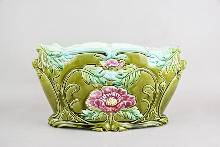 Fantastic ceramic planter or jardinière from France, circa 1910. This floral designed planter or jardinière just looks fantastic in combination with the wonderful worked blossoms on the front and the back. A great coloring and the unique shape makes