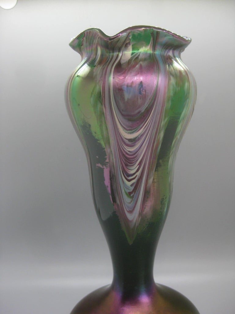 Stunning Art Nouveau Czech Bohemian iridescent pulled feather art glass vase by Josef Rindskopf, circa early 1900s. The vase has wonderful color and design. Green clear glass body with an opaque pulled feather design. Handmade and has a polished
