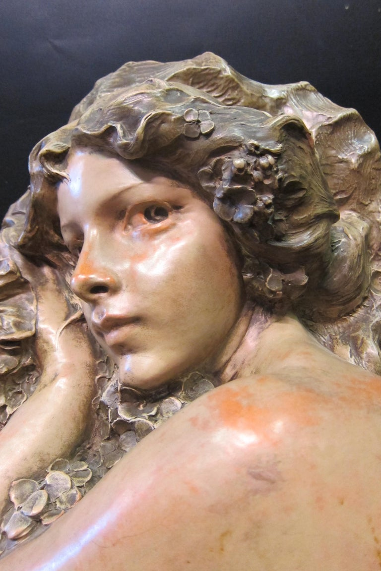 This vintage Art Nouveau figural sculpture is executed in terra cotta. It depicts a beautiful young woman, with expressive eyes, embracing floral blooms. The work is signed