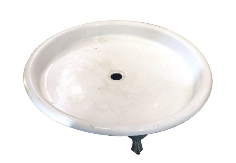 A beautiful and unusual round shaped shower tray in white cast iron with four feet in the shape of a paw. Cast iron, green painting in the front, France, circa 1900.