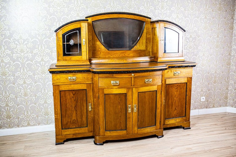 We present you a big, representative oak and oak burl sideboard from the turn of the 19th and 20th centuries. This piece of furniture is composed of a four-leaf base, with a central section advanced in the avant-corps manner, and a removable add-on