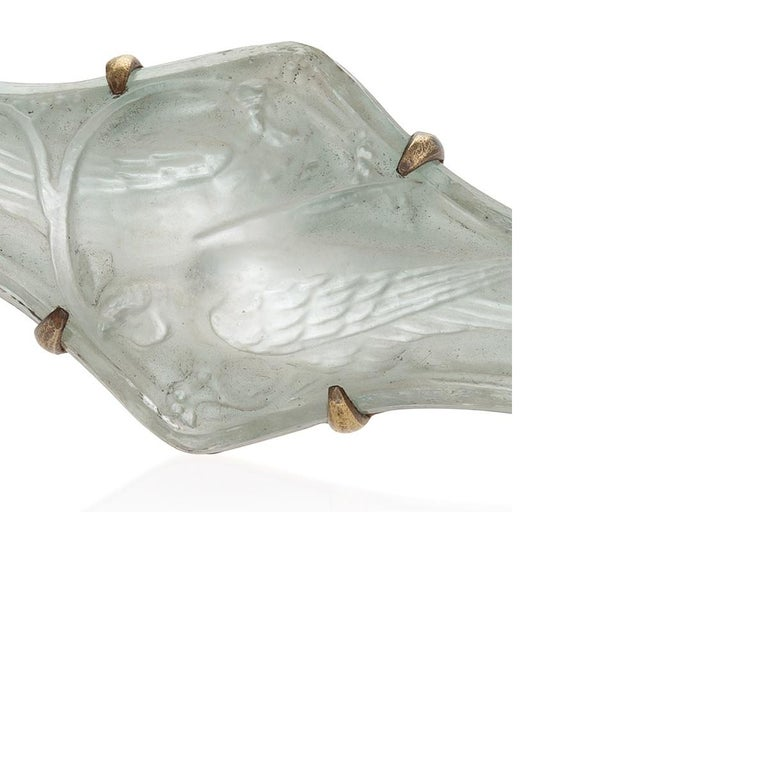 A French Art Nouveau silver foil-backed molded glass brooch set in brass. The molded glass features a motif of embracing pheasants with elongated, twisting tail feathers. Circa 1900.  Signed LALIQUE.   Pictured in Rene Lalique maitre-verrier