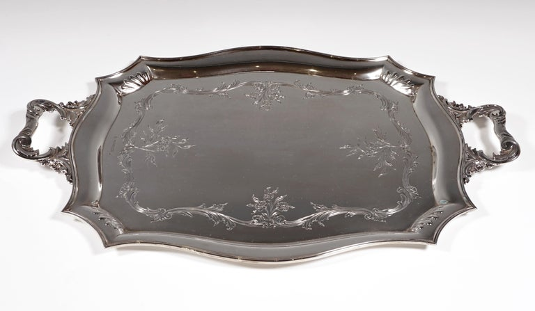 Silver tray in a rectangular basic shape with bevelled corners, accentuated by embossed hump decoration and curved, profiled edges, on the mirror, encircling volute and flower band, two volute handles with floral decoration on the short