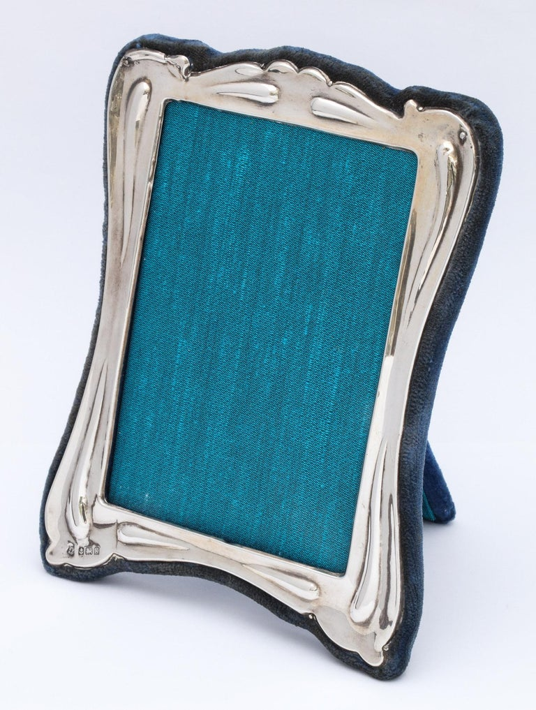 Art Nouveau, sterling silver picture frame, Birmingham, England, 1906, Boots Pure Drug Company - maker. Retailed at Boots. Backed in dark blue velvet. Measures 7 1/4 inches high (at highest point) x 5 3/4 inches wide (at widest point) x 3 1/2 inches