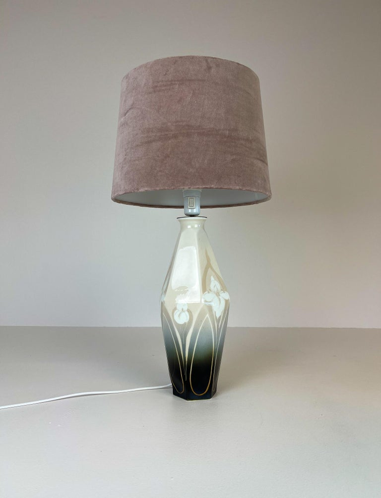 This rare table lamp was made in the begging at 1900. Made at Rörstrand factory and designed by Astrid Ewerlöf. The lamp has a wonderful shaped body with the typical Art Nouveau flowers. New shade in velvet.   Good condition, rewired.  Measures:
