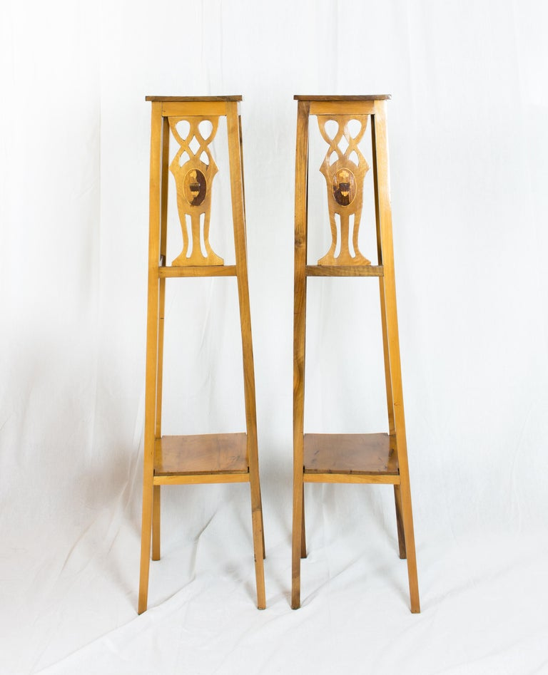 A set of two Art Nouveau flower stands in solid walnut. The flower stands also have a shelf at the bottom. On two sides of the stands there are 2 Art Nouveau wood pictures in the form of a marquetry. The marquetry was apparently reworked sometime.