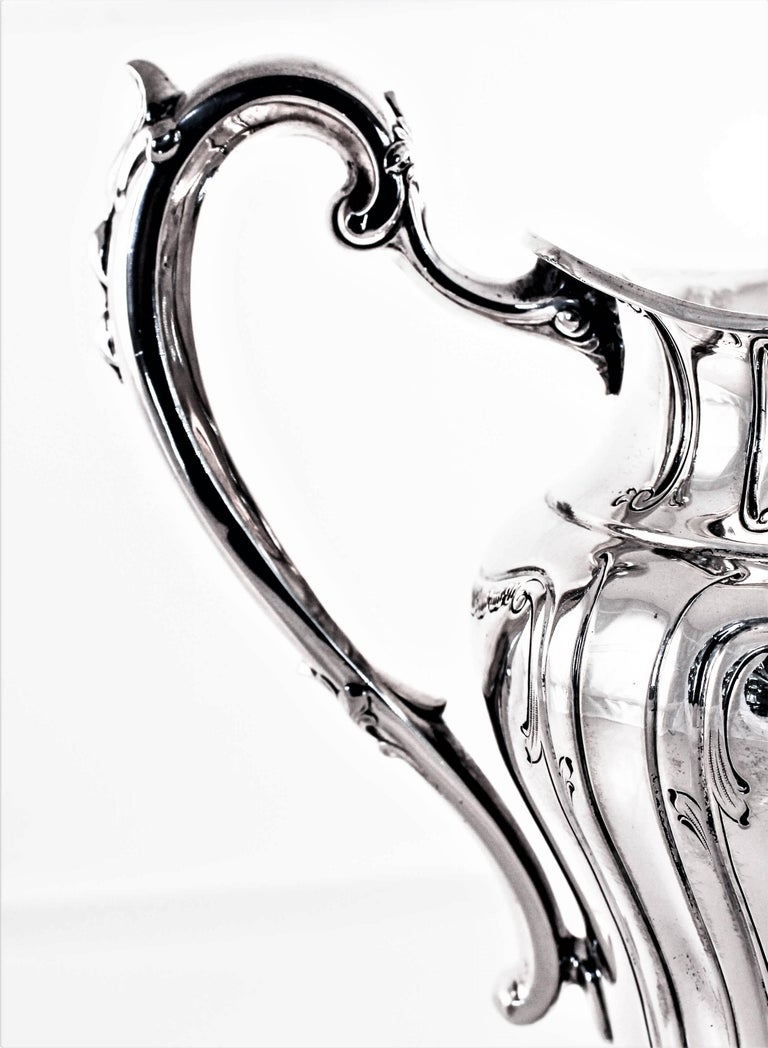 We are proud to offer this magnificent water pitcher from the early 20th century. The body and handle have that natural curvature that was popular at that period. There is etching and indentations throughout and a lovely hand engraved monogram (MM)